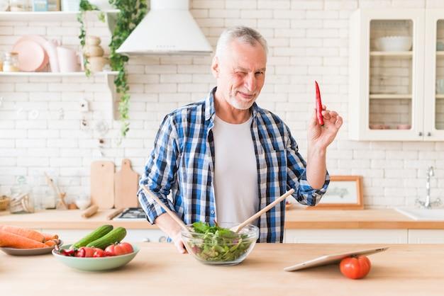 Älterer mann, der sein auge blinzelt, das in der hand den pfeffer des roten paprikas zubereitet den salat zubereitet