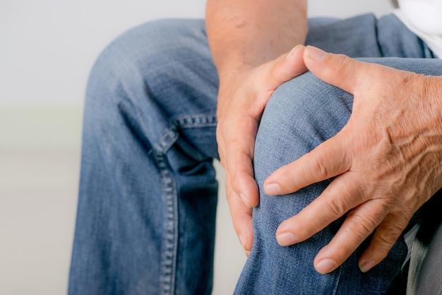 Älterer mann, der sein knie durch die schmerz der arthritis berührt. welttag der senioren.