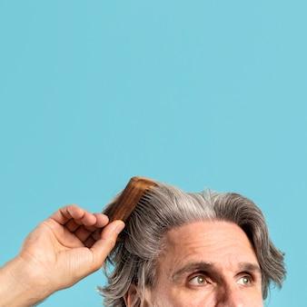 Älterer mann, der seine haare mit kopierraum kämmt