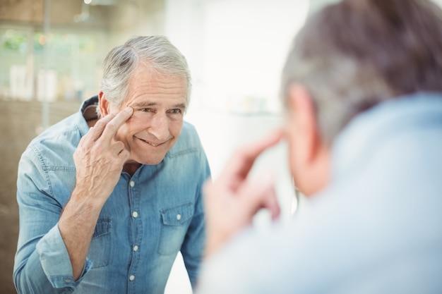 Älterer mann, der seine haut im spiegel betrachtet