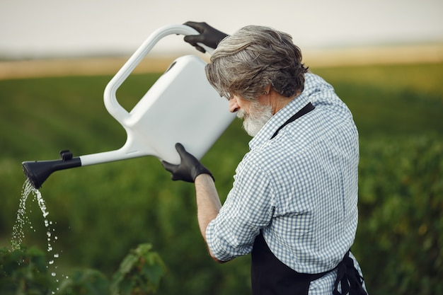 Älterer mann, der seine pflanzen in seinem garten mit streusel gießt. mann in einer schwarzen schürze.