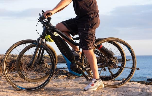 Älterer mann, der seinen bici auf den klippen reitet. horizont über meer bei sonnenuntergang. zwei elektrofahrräder mit batterie und motor. eine person in aktivität