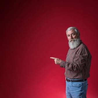Älterer mann, der seinen finger auf etwas gegen roten hintergrund zeigt