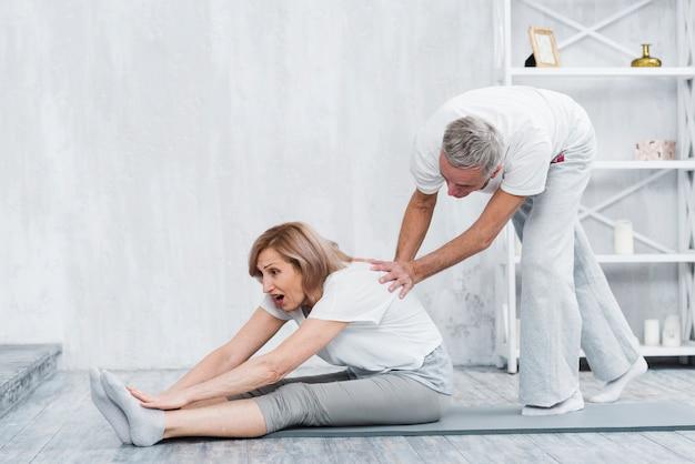Älterer mann, der seiner frau hilft, yogaposition zu tun