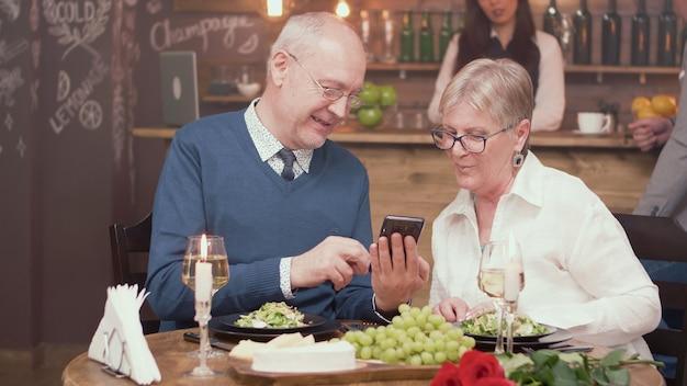 Älterer mann, der seiner frau in einem restaurant etwas auf seinem telefon zeigt. fröhliches älteres paar. romantisches paar.