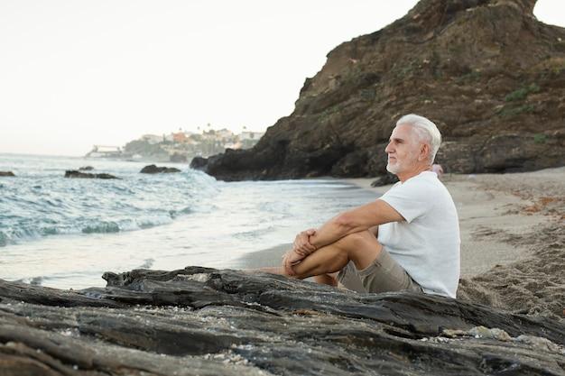 Älterer mann, der sich am strand ausruht und das meer bewundert