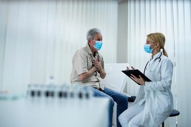 Älterer mann, der sich über brustschmerzen beschwert, während arzt symptome im krankenhausbüro aufschreibt.