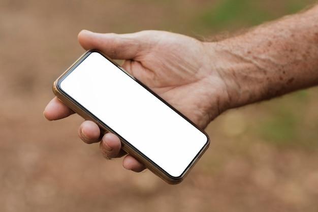 Älterer mann, der smartphone mit weißem bildschirm hält