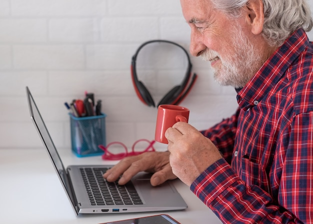 Älterer mann, der social-media-inhalte mit laptop auf weißem schreibtisch durchsucht und eine kaffeetasse trinkt