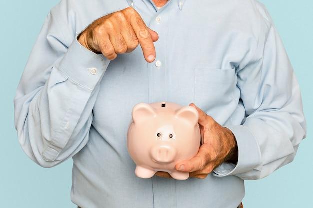Älterer mann, der sparschwein für finanzsparkampagne hält