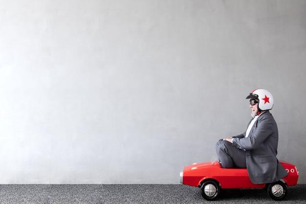 Älterer mann, der spielzeugauto reitet