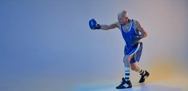 Älterer mann, der sportbekleidungsboxen lokalisiert auf gradientenstudiowand trägt