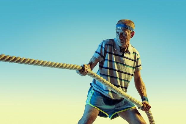 Älterer mann, der sportbekleidungstraining mit seilen auf gradientenhintergrund, neonlicht trägt.