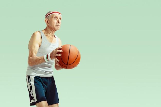 Älterer mann, der sportkleidung trägt, die basketball auf grün spielt