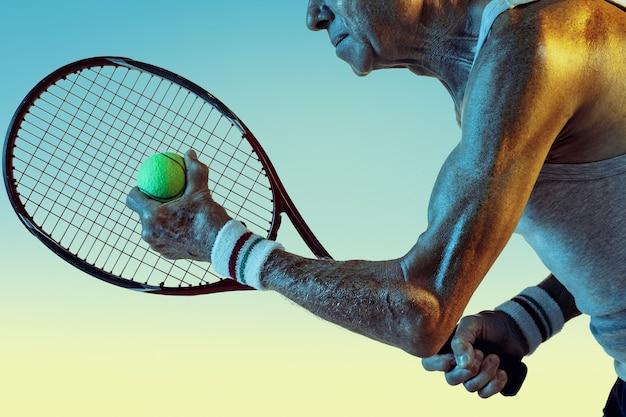 Älterer mann, der sportkleidung trägt und tennis auf farbverlaufshintergrund spielt, neonlicht. kaukasisches männliches model in toller form bleibt aktiv und sportlich. konzept von sport, aktivität, bewegung, wohlbefinden, vertrauen.