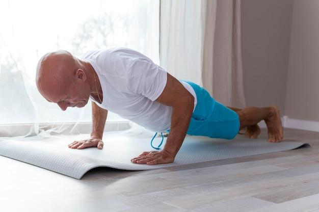 Älterer mann, der sportübungen neben seinem fenster macht