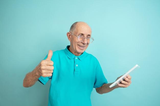 Älterer mann, der tablette benutzt und daumen aufgibt