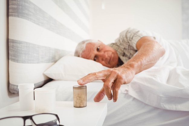 Älterer mann, der tablettenfläschchen beim schlafen im schlafzimmer aufhebt