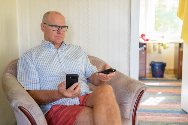 Älterer mann, der telefon beim fernsehen zu hause hält