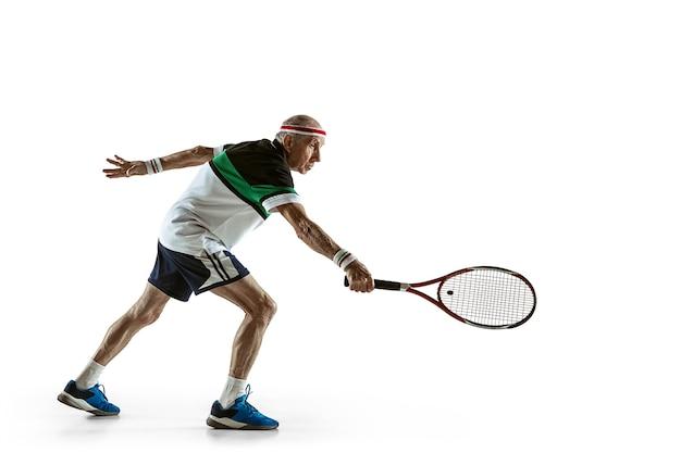 Älterer mann, der tennis in sportkleidung spielt, isoliert auf weißem hintergrund