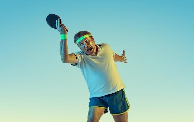 Älterer mann, der tischtennis auf gradientenwand im neonlicht spielt. das kaukasische männliche model in guter form bleibt aktiv und sportlich. konzept von sport, aktivität, bewegung, wohlbefinden, gesundem lebensstil.