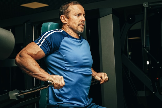 Älterer mann, der übungen für arme in einer trainingsmaschine im fitnessstudio macht