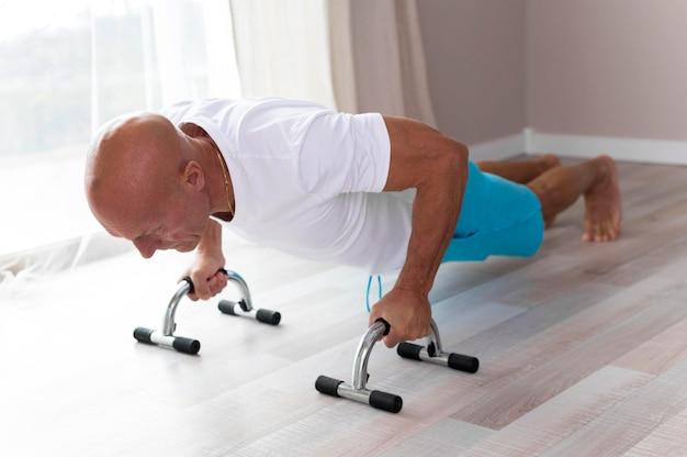 Älterer mann, der übungen zu hause macht