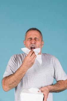 Älterer mann, der ungefähr seidenpapier hält, um auf blauem hintergrund zu niesen