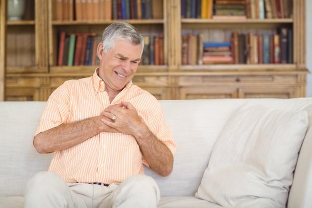 Älterer mann, der unter brustschmerzen im wohnzimmer leidet