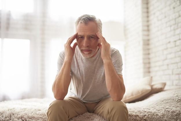 Älterer mann, der unter kopfschmerzen-anschlag-symptom leidet