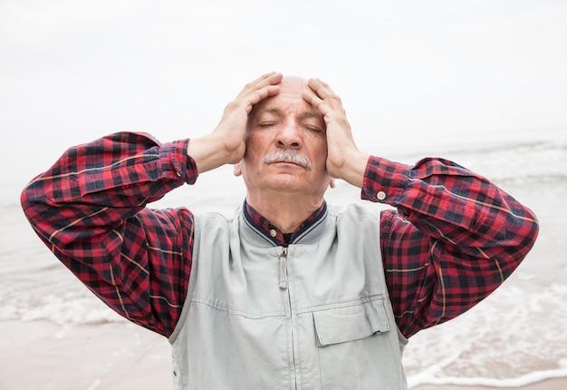 Älterer mann, der unter kopfschmerzen auf seehintergrund leidet