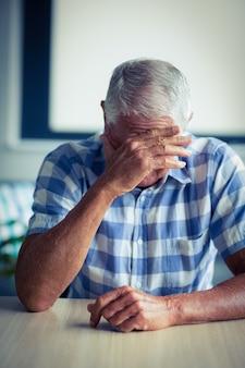 Älterer mann, der unter kopfschmerzen leidet