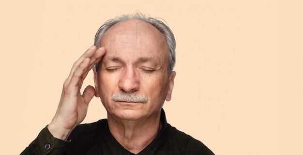 Älterer mann, der unter kopfschmerzen leidet.