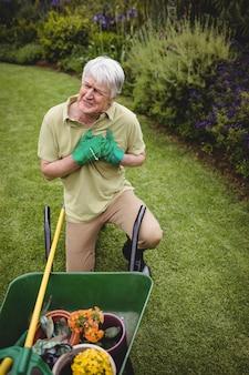 Älterer mann, der unter schmerzen während der gartenarbeit leidet