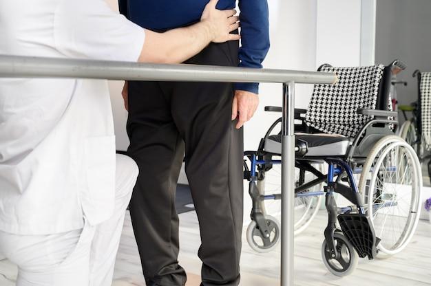 Älterer mann, der vom physiotherapeuten im reha-zentrum unterstützt wird.