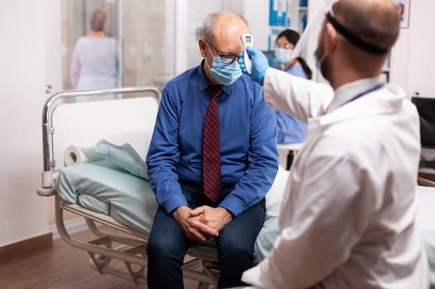 Älterer mann, der während der coronavirus-pandemie im untersuchungsraum des krankenhauses seine temperatur bekommt