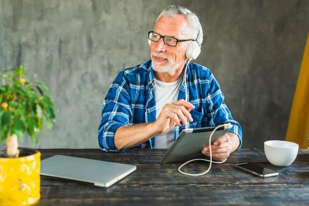 Älterer mann, der weg hörende musik durch kopfhörer auf digitaler tablette schaut