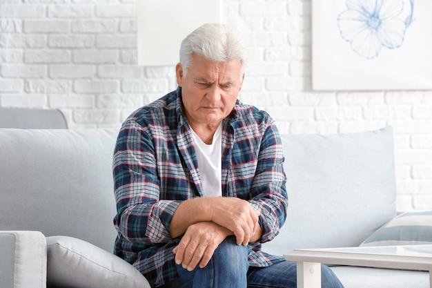 Älterer mann, der zu hause an parkinson leidet