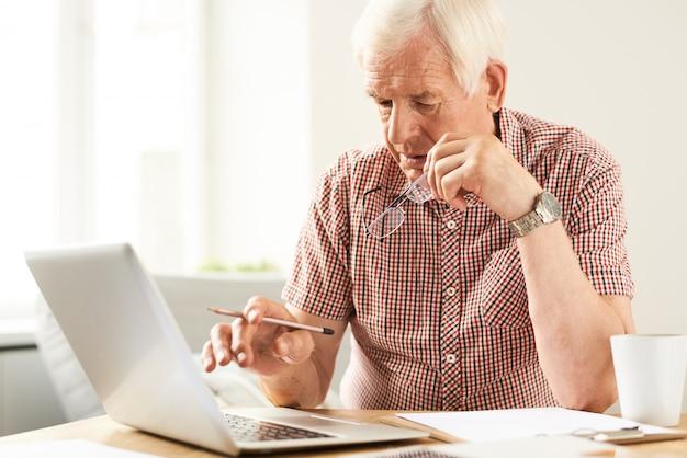 Älterer mann, der zu hause arbeitet
