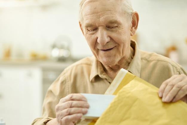 Älterer mann, der zu hause ein postpaket auspackt
