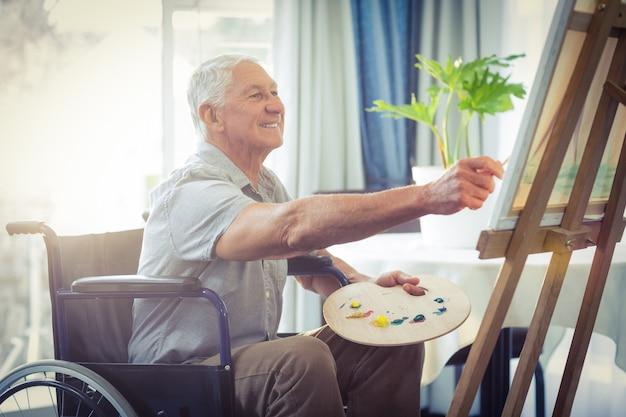 Älterer mann, der zu hause malt
