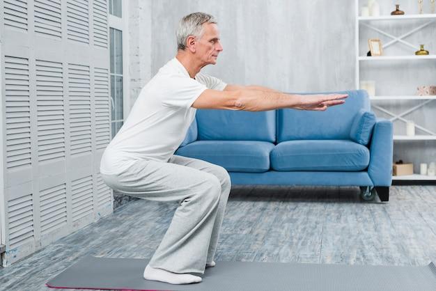 Älterer mann, der zu hause trainiert