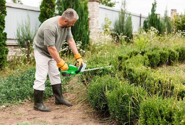 Älterer mann, der zutatwerkzeug auf busch verwendet