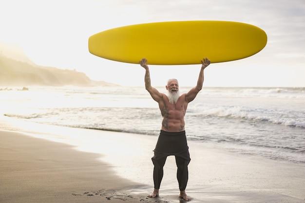 Älterer mann des hipster-surfers, der longboard auf tropischem inselstrand hält - fokus auf gesicht
