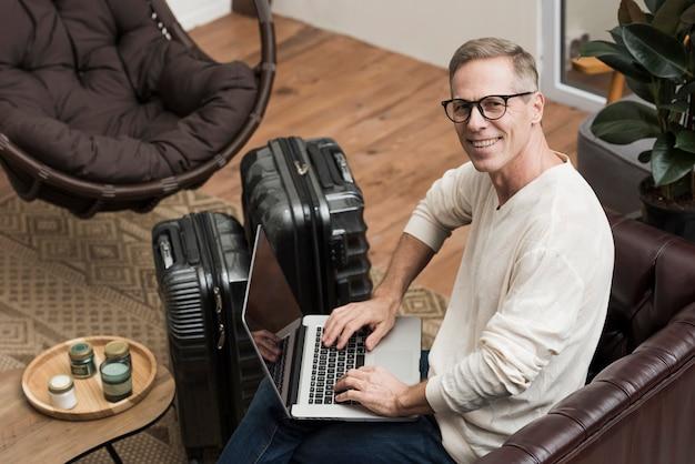 Älterer mann des hohen winkels, der durch seinen laptop schaut