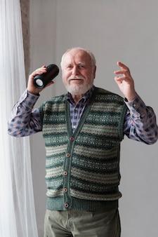 Älterer mann des niedrigen winkels, der sprecher hält