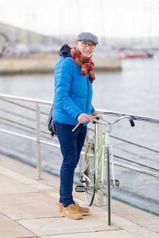 Älterer mann des portraits, der mit seinem fahrrad in der straße geht