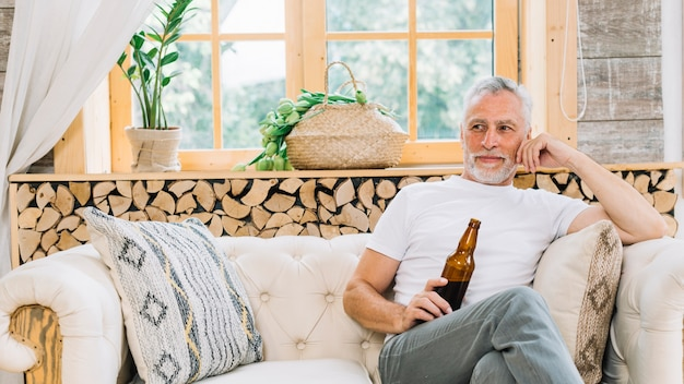 Älterer mann des ruhestandes, der die bierflasche sitzt auf sofa hält