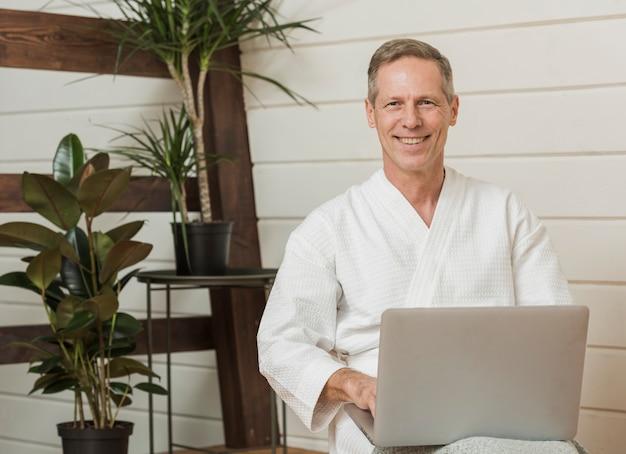 Älterer mann des smiley, der an seinem laptop arbeitet