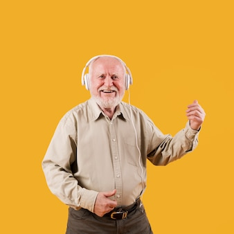 Älterer mann des smiley, der eingebildeten quitar spielt